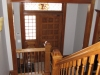 The original apartment entry stair has been opened up to become the main interior stair. The wall separating the stair from the hall was been cut down to permit open railings.  The newel at the bottom is new, made to match original newels.